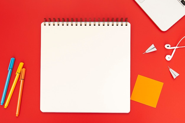 Top view arrangement of desk elements on red background Free Photo