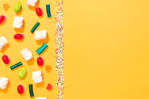 コピースペースと黄色の背景に異なる色のキャンディーの平面図配置 無料写真