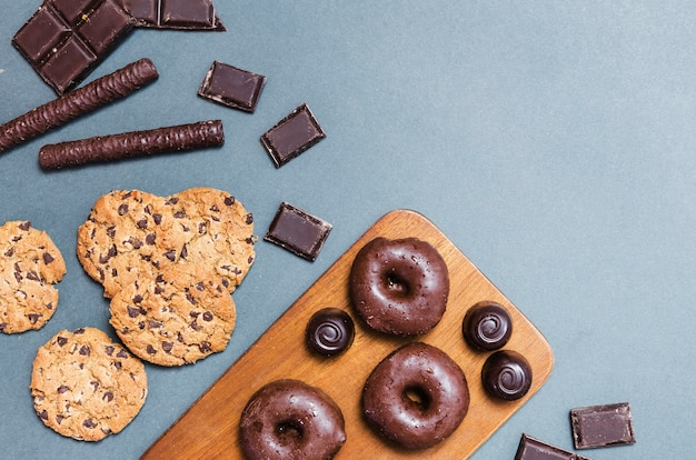 Top view arrangement with donuts on cutting board Free Photo