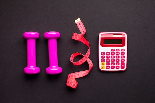 Top view arrangement with dumbbells and calculator Free Photo