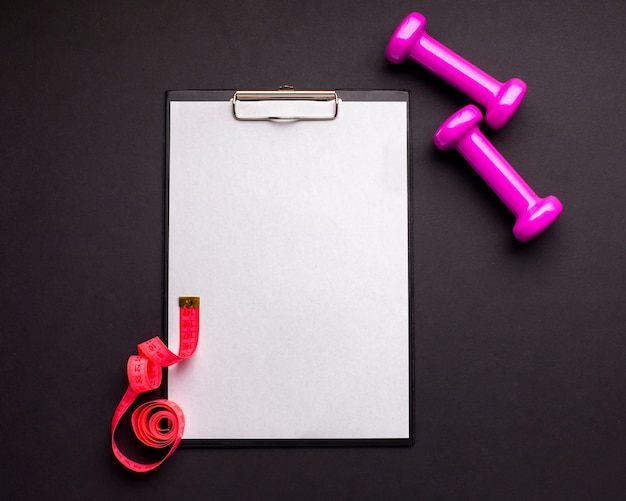 Top view arrangement with dumbbells and clipboard Free Photo