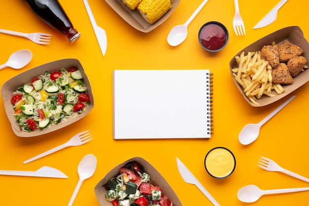 Top view arrangement with food, tableware and notebook Free Photo