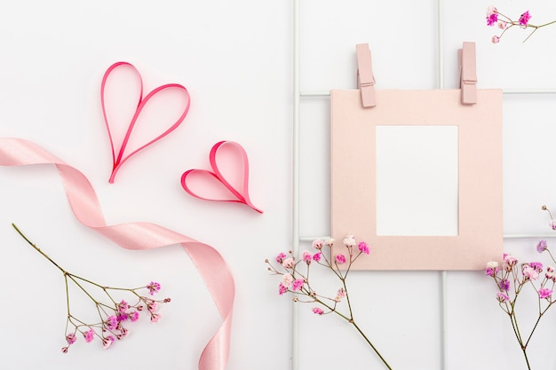 Top view arrangement with frame and heart shapes Free Photo