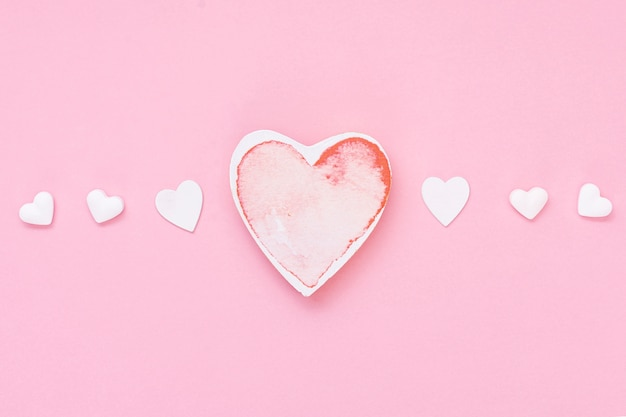 Top view arrangement with heart shaped cookies and pink background Free Photo