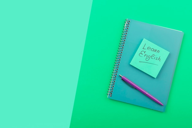 Top view arrangement with notebook on green background Free Photo
