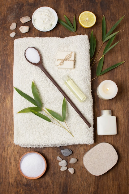 Top view arrangement with plant and spoon on towel Free Photo