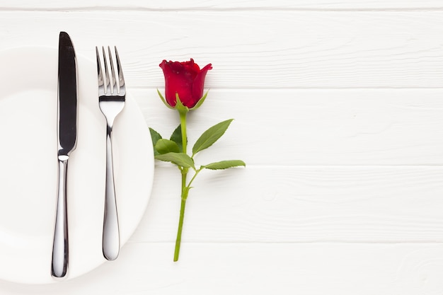 Top view arrangement with plate, cutlery and rose Free Photo