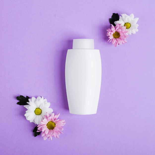 Top view arrangement with white bottle and flowers Free Photo