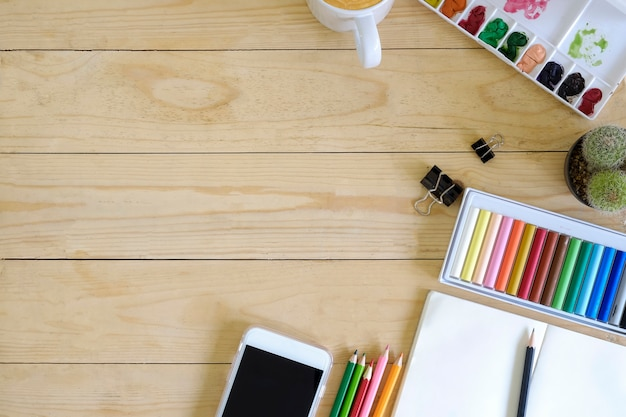 Top view artist workspace smartphone, colour, mug of coffee, notepad paper, cactus and pencil on wooden table Premium Photo