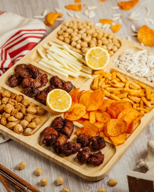 Top view of assorted beer snacks as fried dushbara grilled chicken  cheese  boiled chickpeas and potato chips on a wooden board Free Photo