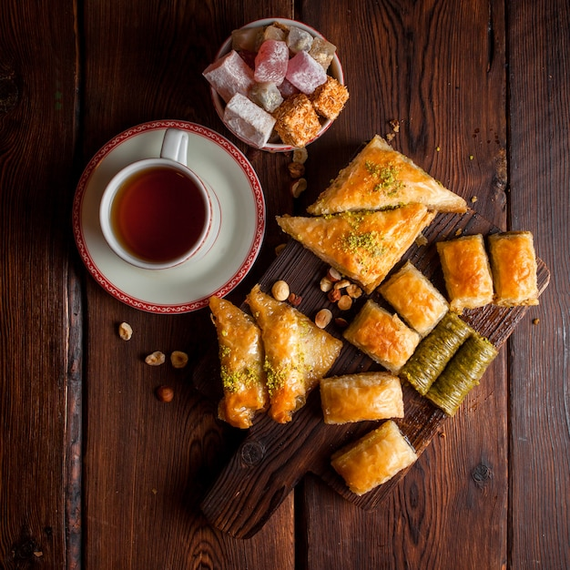 Top view assorted turkish baklava with cup of tea and turkish delight in wooden plank Free Photo