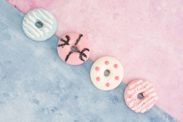 Top view of assortment of colorful glazed doughnuts Free Photo