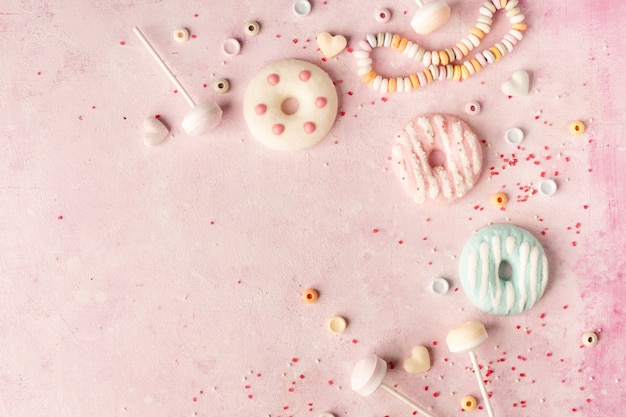 Top view of assortment of glazed doughnuts and candy with copy space Free Photo