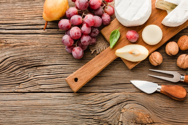 Top view assortment of gourmet cheese on wooden cutting board with grapes and ustensils Free Photo