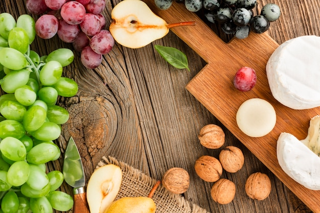 Top view assortment of gourmet cheese on wooden cutting board with grapes and walnuts Free Photo