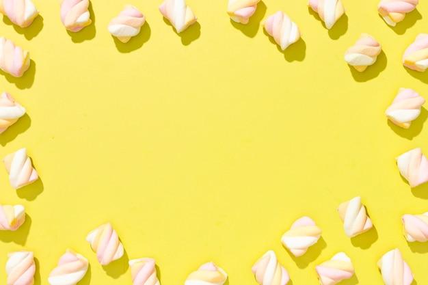コピースペースと黄色の背景にカラフルなキャンディーの上面品揃え 無料写真