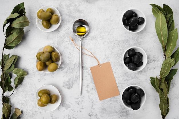 Vista dall'alto assortimento di olive e olio Foto Gratuite