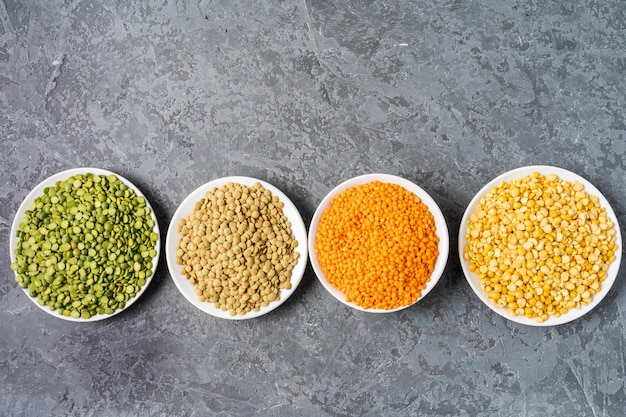Top view of assortment of peas, lentils and legumes over gray background. Premium Photo