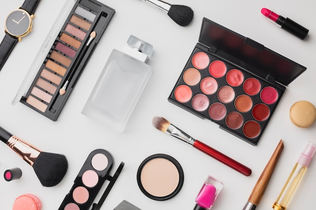 Top view assortment with make-up palette and perfume Free Photo