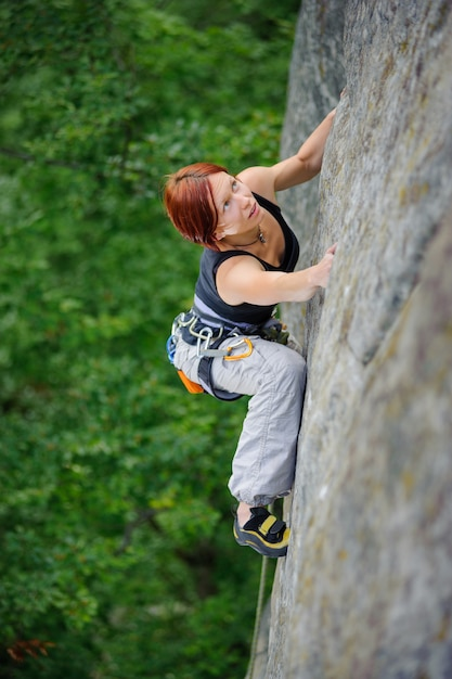 Top view of athletic woman climbing steep cliff wall Premium Photo