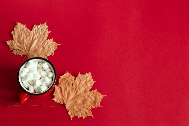 Top view autumn maple leaves and cup with marshmallows copy space background Premium Photo