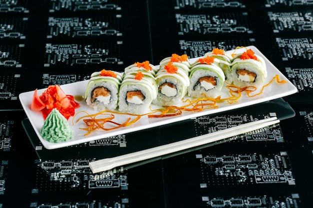 Vista dall'alto di involtini di sushi di avocado con salmone condita con tobiko rosso Foto Gratuite