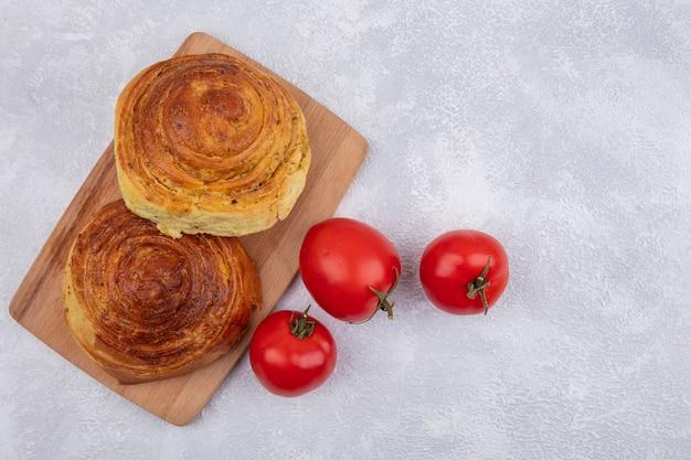 Vista dall'alto della pasticceria tradizionale azera gogal su una tavola da cucina in legno con pomodori freschi isolato su uno sfondo bianco con spazio di copia Foto Gratuite