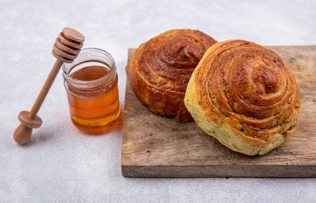 Vista dall'alto della pasticceria tradizionale azera gogal su una tavola da cucina in legno con miele su un vasetto di vetro su sfondo bianco Foto Gratuite