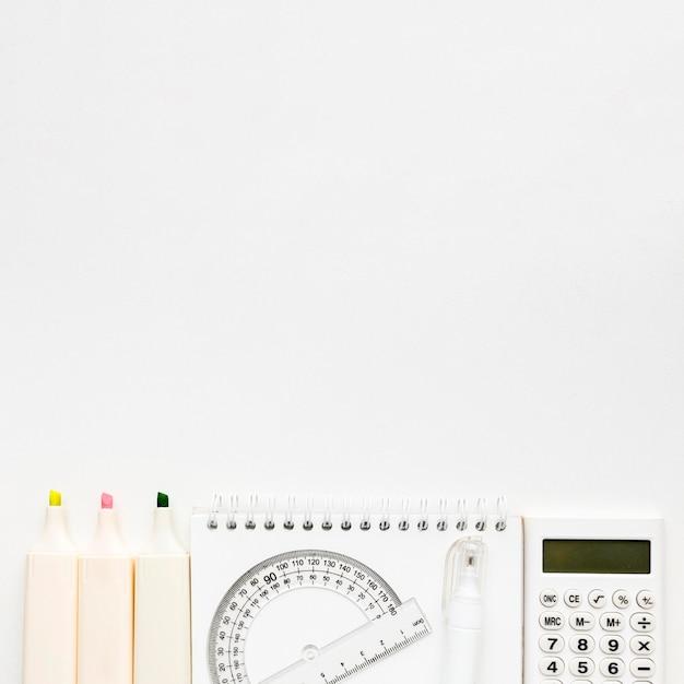 Vista dall'alto di ritorno a scuola elementi essenziali con calcolatrice e taccuino Foto Gratuite