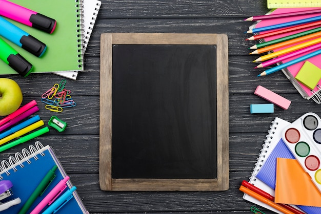 Top view of back to school stationery with colorful pencils and blackboard Free Photo