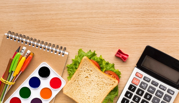 Top view of back to school supplies with calculator and sandwich Free Photo