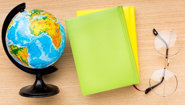 Top view of back to school supplies with glasses and globe Free Photo