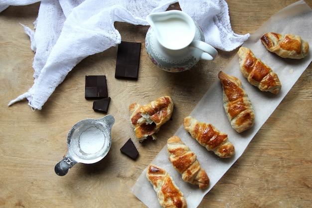 Вид сверху рогалики с джемом кувшин с молочным шоколадом и мукой с марлей Бесплатные Фотографии