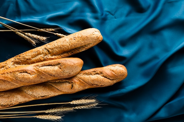 Top view of baguette and wheat on blue material Free Photo