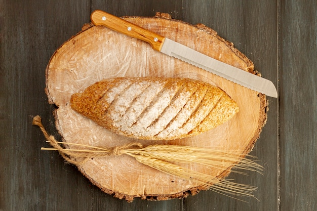 Top view baked bread with knife Free Photo