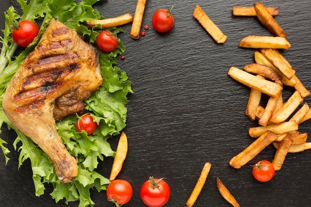 상위 뷰 구운 닭고기와 체리 토마토와 감자 튀김 프리미엄 사진