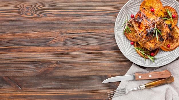 칼 붙이 및 복사 공간 접시에 구운 닭고기와 오렌지 슬라이스 상위 뷰 무료 사진