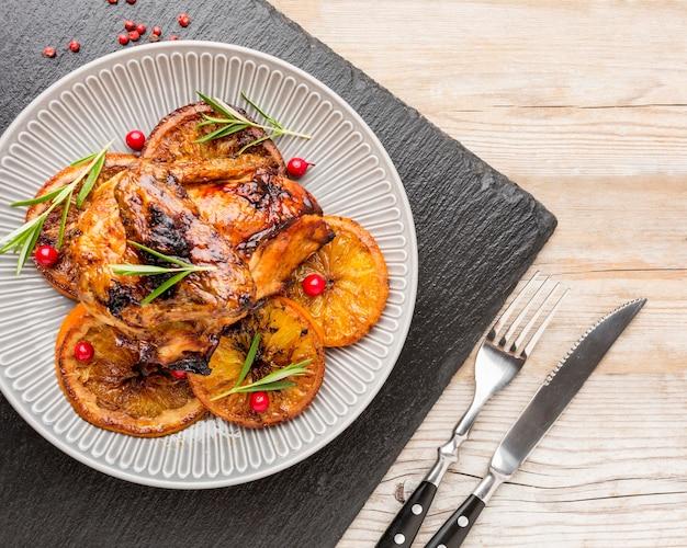 칼 붙이 접시에 구운 닭고기와 오렌지 슬라이스 상위 뷰 무료 사진