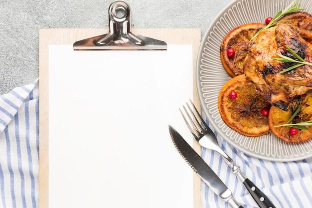 주방 수건 및 빈 클립 보드와 함께 접시에 구운 닭고기와 오렌지 슬라이스 상위 뷰 무료 사진