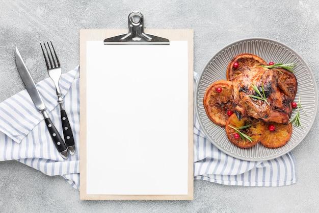 상위 뷰 구운 닭고기와 오렌지 슬라이스 주방 수건 및 빈 메모장 접시에 무료 사진