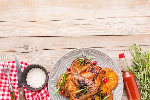 바다 소금과 소스와 함께 접시에 구운 닭고기와 오렌지 슬라이스 상위 뷰 무료 사진