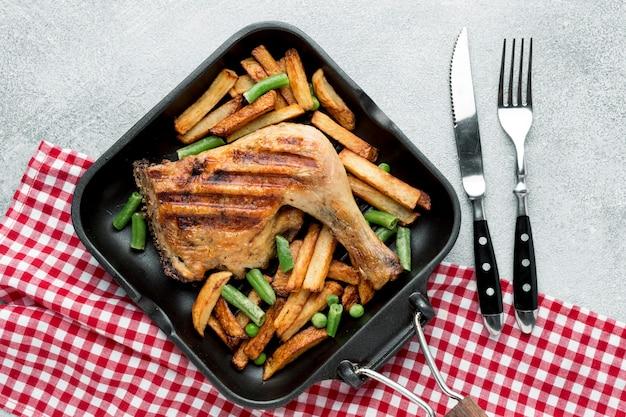 칼 붙이 냄비에 구운 닭고기와 감자 상위 뷰 프리미엄 사진