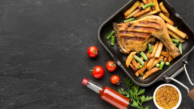 토마토와 복사 공간 냄비에 구운 닭고기와 감자 상위 뷰 무료 사진