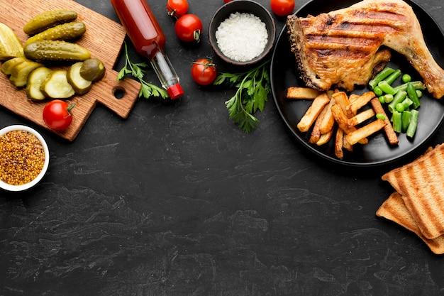Вид сверху запеченный цыпленок и картофель на тарелке с солеными огурцами и копией пространства Premium Фотографии