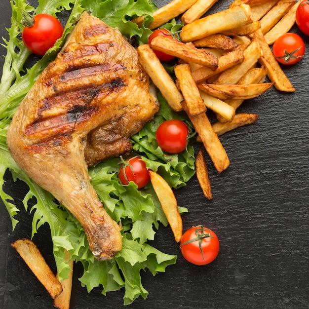 Вид сверху запеченный цыпленок и помидоры с картофелем фри Premium Фотографии