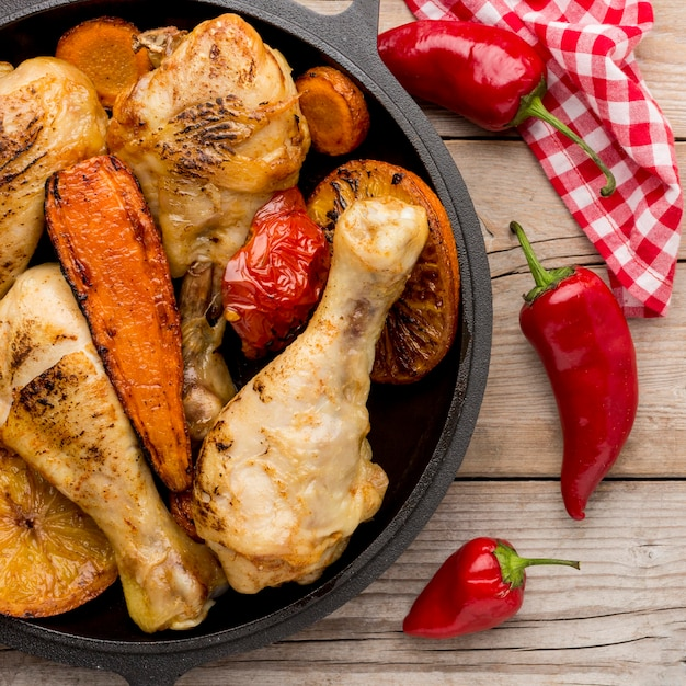 Вид сверху запеченный цыпленок и овощи на сковороде с красным перцем Premium Фотографии