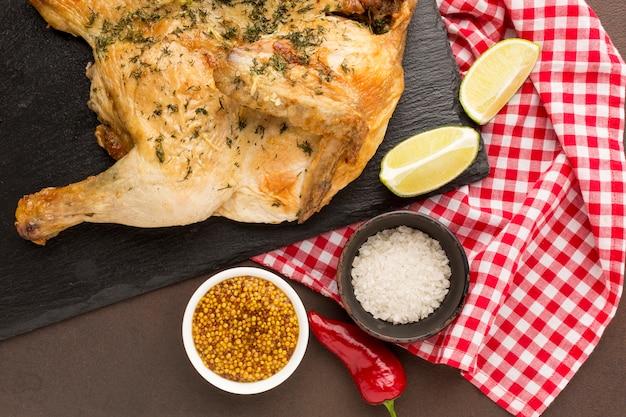 Вид сверху запеченный цыпленок на разделочной доске с приправами Бесплатные Фотографии
