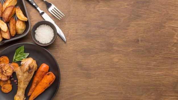 Vista dall'alto pollo al forno e verdure sulla piastra con spicchi e copia-spazio Foto Gratuite