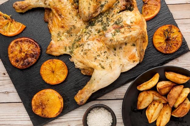 오렌지 슬라이스와 웨지와 상위 뷰 구운 치킨 무료 사진