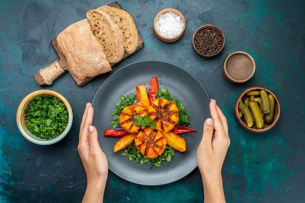 Vista dall'alto patate al forno con carne macinata e verdure all'interno del piatto con pane sulla scrivania blu scuro. Foto Gratuite